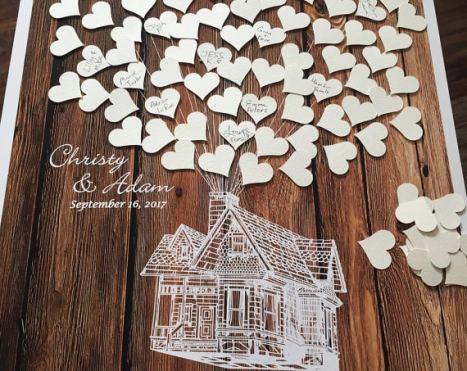 Στο συγκεκριμένο, ξύλινο ευχολόγιο γάμου οι καλεσμένοι μπορούν να γράψουν τις ευχές τους πάνω σε καρδιές ή πάνω σε μπαλόνια